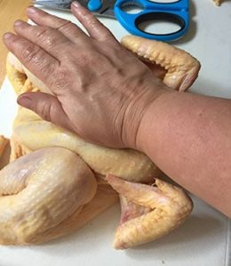 Press down firmly on the breast bone to flatten the chicken.