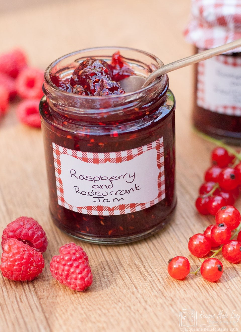Open jar of raspebrry and redcurrant jam by recipes made easy. Spoon in jar and surrounded by raspberries and redcurrants.