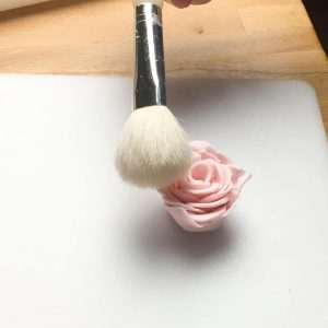 using a brush to open out the petals